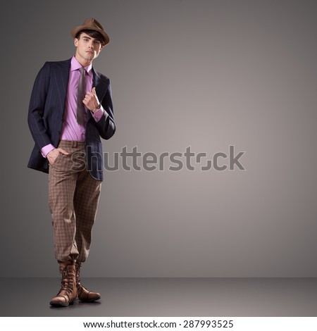 Attractive young male model dressed in vintage clothes isolated on gray background - stock photo