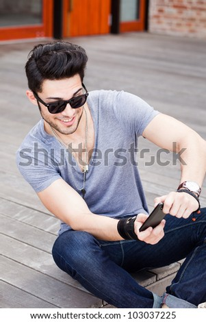 attractive young male model playing games on a smart-phone - stock photo