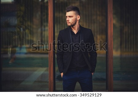 attractive young male model posing outdoors in black jacket and shirt - stock photo