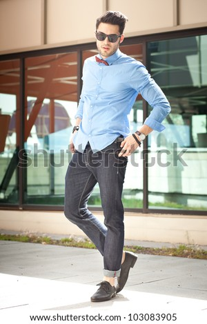 attractive young male model posing outdoors in blue shirt and sunglasses - stock photo