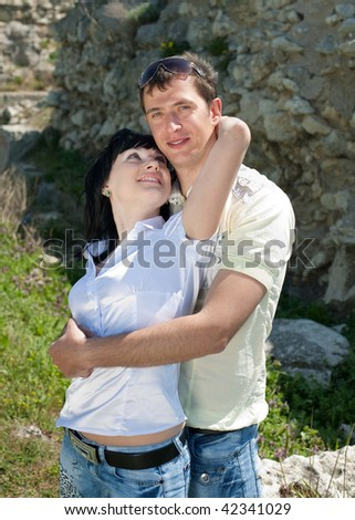 Attractive young man and woman are playing outdoors