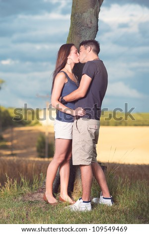 attractive young man and woman kissing outdoors - stock photo