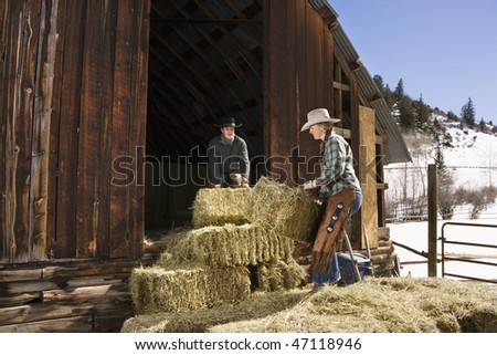 Attractive young man and woman lifting hay bales on a farm in front of a barn. Horizontal shot.