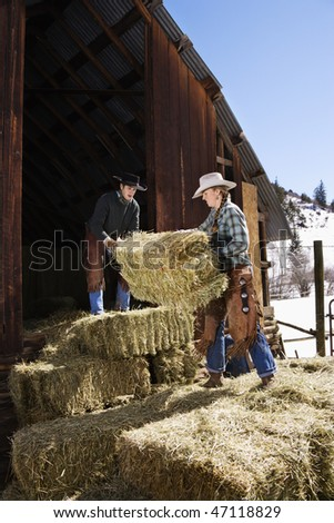 Attractive young man and woman lifting hay bales on a farm in front of a barn. Vertical shot. - stock photo
