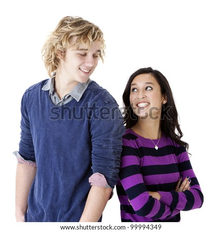 attractive young man and woman standing back to back and looking at one another - stock photo