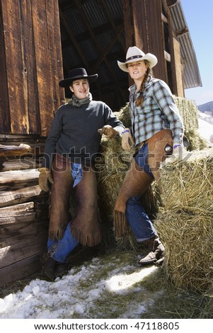 Attractive young man and woman standing in front of hay bales near a barn. Vertical shot. - stock photo
