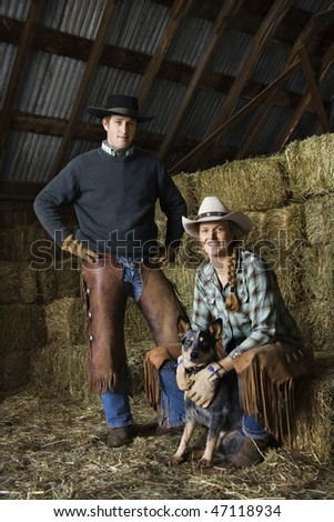 Attractive young man and woman with an Australian Shepherd in a barn. Bales of hay are in the background. Vertical shot. - stock photo