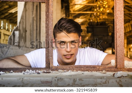 Attractive young man at rusty window with happy expression on his face, looking in camera - stock photo
