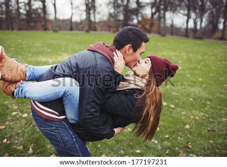 Attractive young man carrying his pretty girlfriend and kissing. Mixed race couple in love outdoors in park. - stock photo