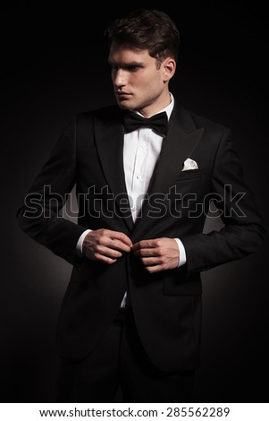 Attractive young man closing his jacket while looking away from the camera. - stock photo