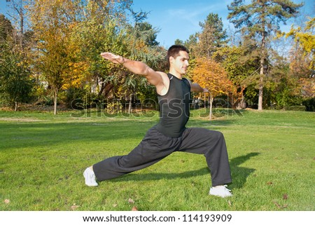 Attractive young man doing exercise in autumn park - stock photo