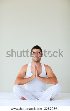 Attractive young man doing yoga in bed with closed eyes - stock photo