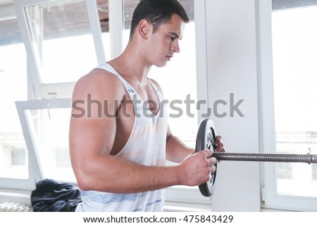 Attractive young man exercising and doing weight lifting at fitness gym. Fitness and health concept.