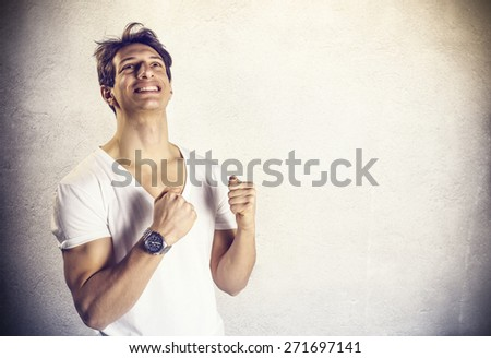 Attractive young man exults - stock photo