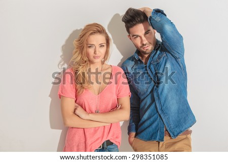 Attractive young man fixing his hair while his girlfriend is holding her hands crossed. - stock photo