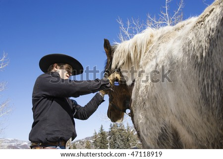 Attractive young man grooming his horse with a snowy mountain landscape in the background. Horizontal shot. - stock photo
