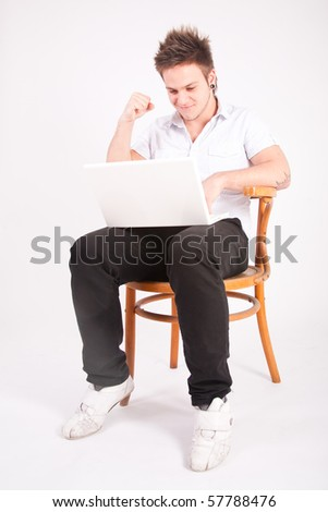 Attractive young man having fun with laptop while sitting on chair