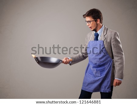 Attractive young man holding a black frying pan - stock photo