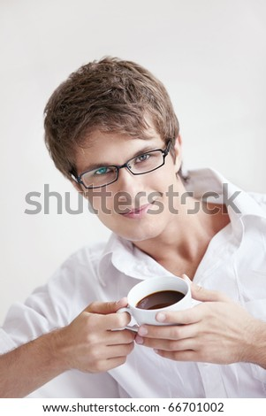 Attractive young man holding a cup of coffee - stock photo