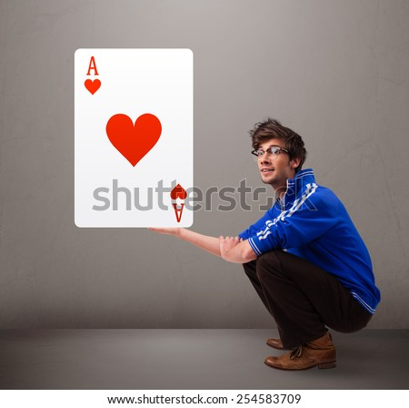 Attractive young man holding a red heart ace - stock photo