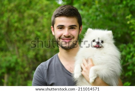 Attractive young man holding german spitz puppy outside and smiling. - stock photo