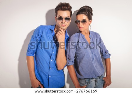 Attractive young man holding his hand to his chin while his lover is looking at the camera. - stock photo
