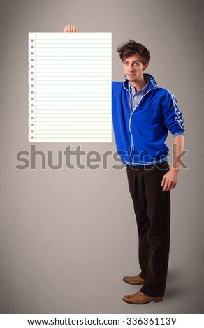 Attractive young man holding white paper copy space with diagonal lines - stock photo