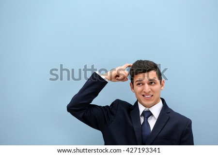 Attractive young man in a suit against light blue wall - stock photo