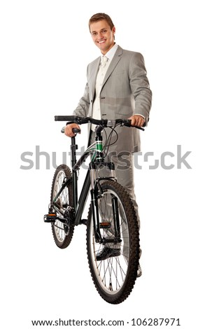 Attractive young man in a suit standing next to a bike and smiling, isolated over white