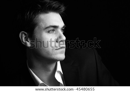 attractive young man in a vintage black and white low key setting - stock photo