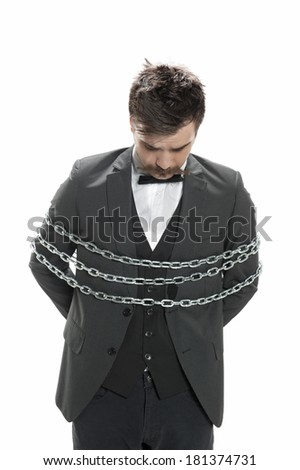 Attractive young man in business suit looks sullen as he stands with chains around him, isolated on white - stock photo