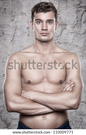 Attractive young man in front of a grey wall - stock photo