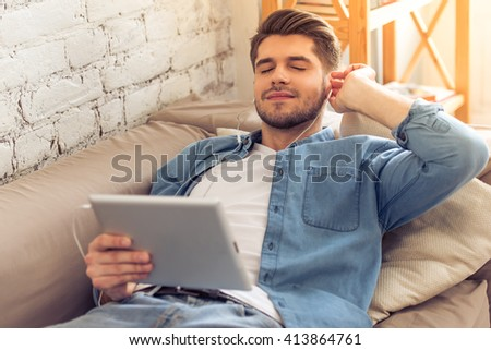 Attractive young man in headphones is listening to music using a tablet and smiling while lying with closed eyes on sofa at home - stock photo