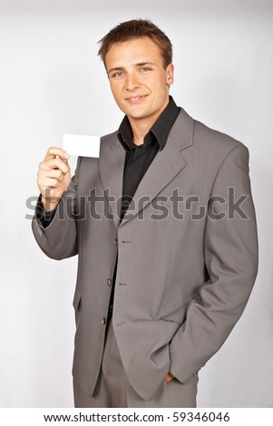 Attractive young man in light suit with business card - stock photo