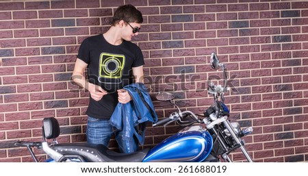 Attractive Young Man in Shades Holding a Jacket While Looking at his Motorcycle on a Brick Wall Background. - stock photo