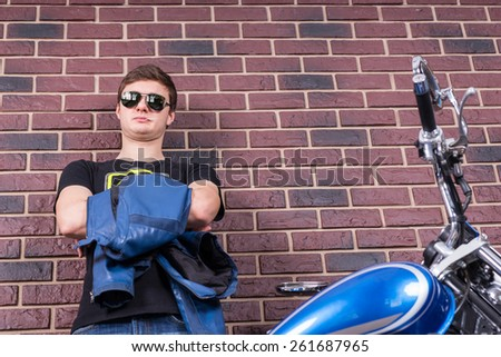 Attractive Young Man in Shades Holding his Jacket Behind his Motorbike on a Brick Wall Background. - stock photo