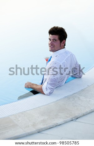 Attractive young man in the pool, having a drink