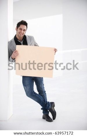 Attractive young man in urban and modern background holding a blank board