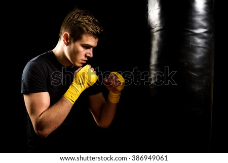 Attractive young man in yellow boxing wraps is training and hitting heavy bag. Fitness, aerobic exercise for active people. Strong athlete boxer isolated on black. Man self defense. - stock photo