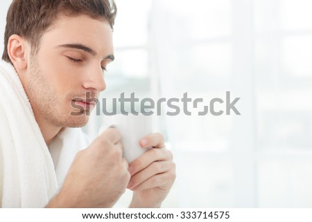 Attractive young man is drinking coffee in the morning. His eyes are closed with pleasure. The man is sitting and relaxing in his bedroom. Copy space in right side - stock photo