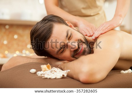 Attractive young man is getting back massage at spa. He is lying and smiling. His eyes are closed with enjoyment - stock photo