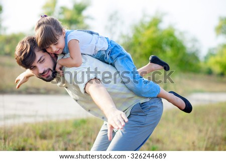 Attractive young man is playing with his daughter in the nature. The father is standing and carrying girl on his back. He is stretching arms sideways. The family is smiling - stock photo