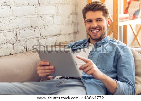 Attractive young man is using a tablet, looking at camera and smiling while lying on sofa at home - stock photo