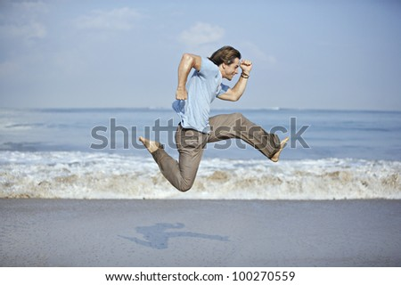 Attractive young man jumping with open legs by the sea shore. - stock photo