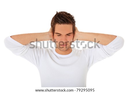 Attractive young man keeps his ears shut. All on white background. - stock photo