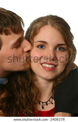Attractive young man kissing beautiful woman on cheek - stock photo