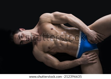 Attractive young man laying on the floor with naked muscular ripped body, hands on briefs - stock photo