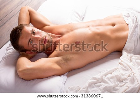 Attractive young man lying in bed - stock photo