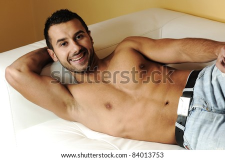Attractive young man on sofa - stock photo