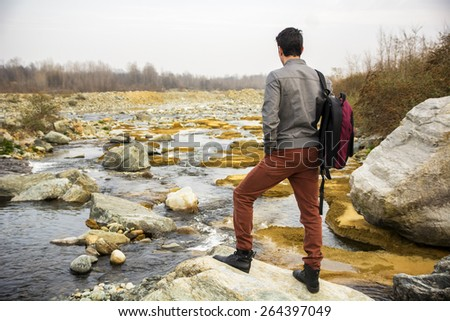 Attractive young man outdoor in nature, at river or water stream, seen from the back, with backpack or rucksack - stock photo